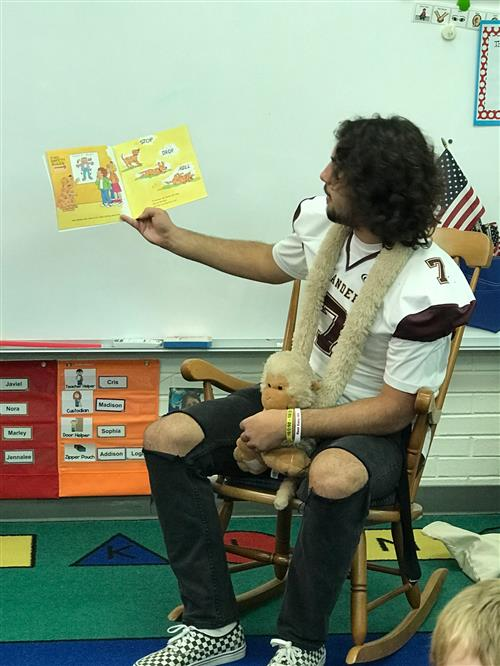 Football player reads to preschool
